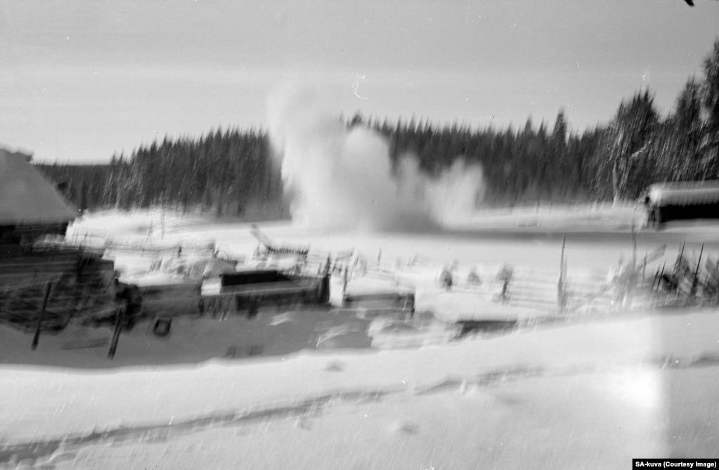 An artillery shell explodes near a farmstead during a Soviet advance.