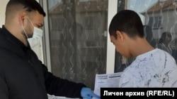 Медиаторът Бойчо Кочев раздава на учениците материали и им обяснява как да ги попълнят