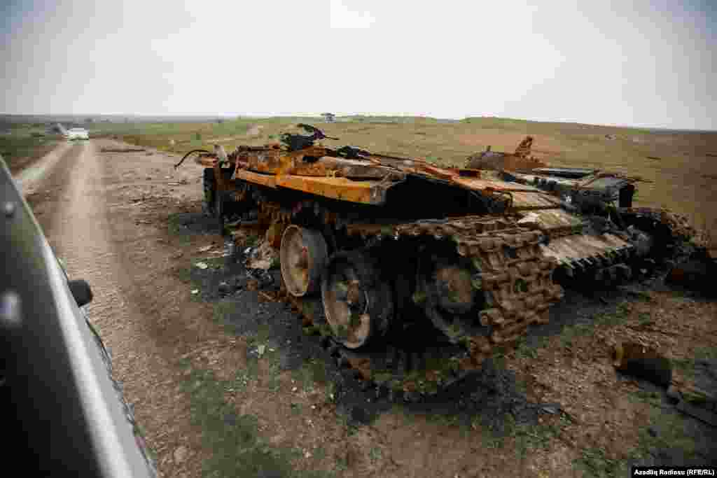A destroyed Armenian tank stands at the side of a road in the Fuzuli district of Azerbaijan.