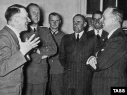 German Foreign Minister Joachim von Ribbentrop (right) talks with Adolf Hitler on his arrival in Berlin after signing the pact in Moscow.