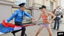 Путинге қарсы акцияға шыққан Femen ұйымының мүшесін полиция ұстап тұр. Киев, 18 шілде 2013 жыл