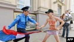 Милиционер пытается отобрать флаг у протестующей активистки Femen в Киеве (18 июля 2013 года)