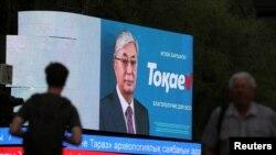 Прохожие рядом с монитором, на котором транслируют предвыборный ролик Касым-Жомарта Токаева. Алматы, 3 июня 2019 года.