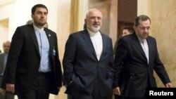 Иран сыртқы істер министрі Мохаммад Джавад Зариф (ортада) АҚШ мемлекеттік хатшысы Джон Керримен кездесуден шығып барады. Швейцария, 17 наурыз 2015 жыл.