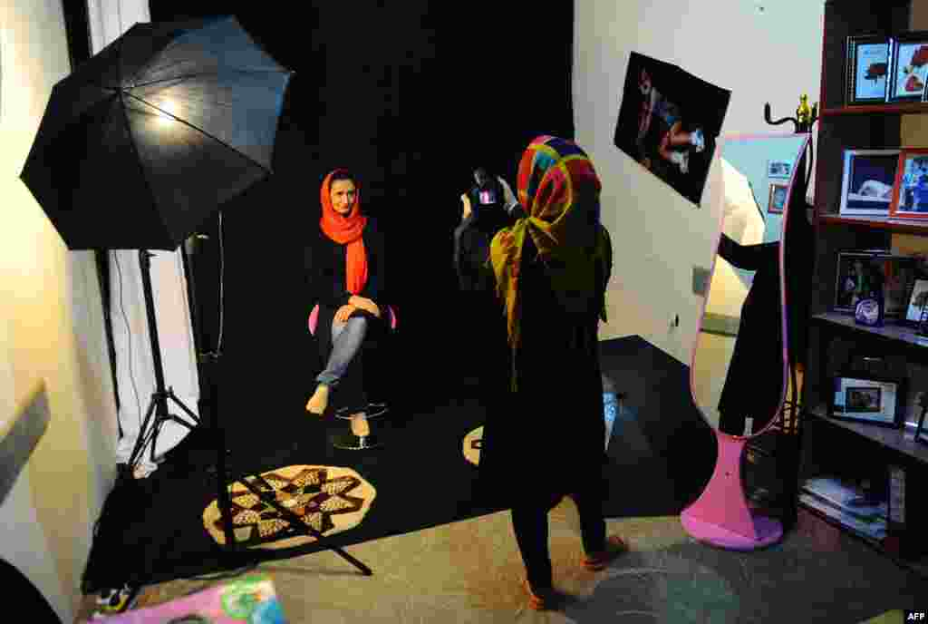 A photographer in Herat, Afghanistan, shoots pictures in her studio. (AFP/Aref Karimi)