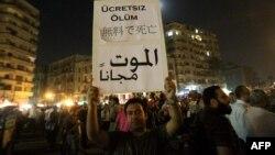 """Тахрир аянтындагы демонстранттардын бири түрдүү тилдерде жазылган """"Баасыз өлүм"""" деген ураанды кармап турат. Каир, 2-июнь 2012"""