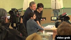 Georgian Prime Minister Giorgi Kvirikashvili, accompanied by his wife and son, votes in parliamentary elections in Tbilisi on October 8 (see video below).