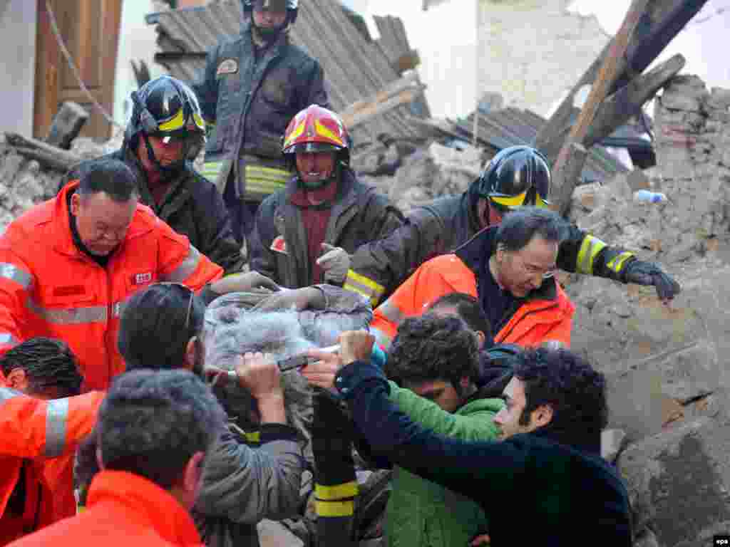Italy - Italian rescue teams retrieve a person from a building which collapsed following an earthquake, in L'aquila, 06Apr2009 - Caption: epa01689457 Italian rescue teams retrieve a person from a building which collapsed following an earthquake, in L'aquila, Central Italy, 06 April 2009. At least nine people were killed 06 April in the central Italian region of Abruzzo when a magnitude-5.8 earthquake struck, police said. Five of the dead were from Castelnuovo, where dozens of houses and a church collapsed, they said in their initial toll from the disaster, which did not include four children that Italian media reported had died in a hospital in LAquila, Abruzzo's capital. Numerous buildings collapsed in LAquila, where people were searching for survivors in the rubble of a house and student dormitory in the citys historic centre. EPA/PERI - PERCOSSI