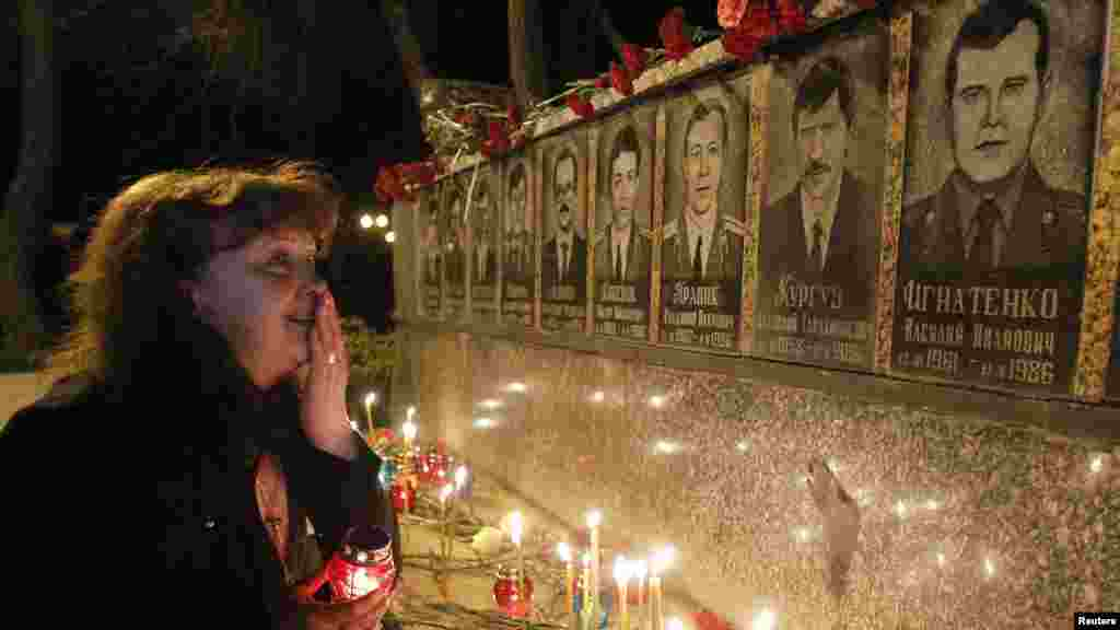A woman cries in front of a memorial dedicated to firefighters and workers who died after the Chornobyl nuclear disaster during a night service near the Chornobyl plant in the city of Slavutych on April 23, 2012.