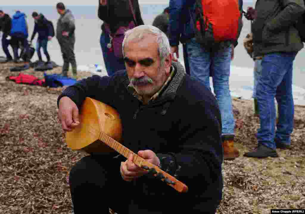 Nazmi Jolak, a Syrian Kurdish farmer, plays his saz after landing on the coast of Lesbos as the refugee boat he arrived on is dismantled behind him. The 52-year-old refugee from Aleppo carried the instrument,wrapped in plastic, across the sea. He is now hoping to join his son in Dortmund, Germany.