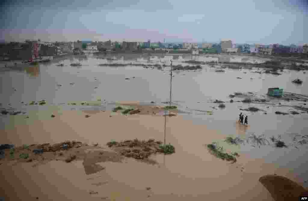 Pakistanis walk through a flooded area in Karachi.