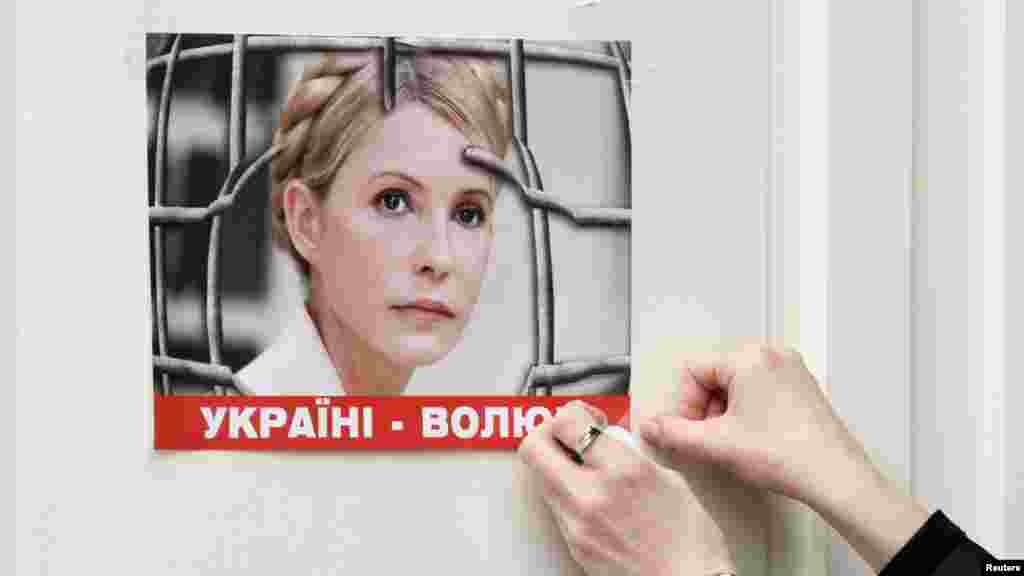 A woman puts a picture in support of jailed Ukrainian opposition leader Yulia Tymoshenko on a Brussels door on March 1, ahead of a two-day European Union leaders summit. (Reuters/Sebastien Pirlet)