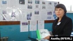 "Укытучы Ләйлә Чумарова ""Мәктәп еллары"" газетасын күрсәтә"