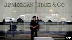 US--A New York City Police office stands at the entrance to the JP Morgan Chase World Headquarters, 15May2012