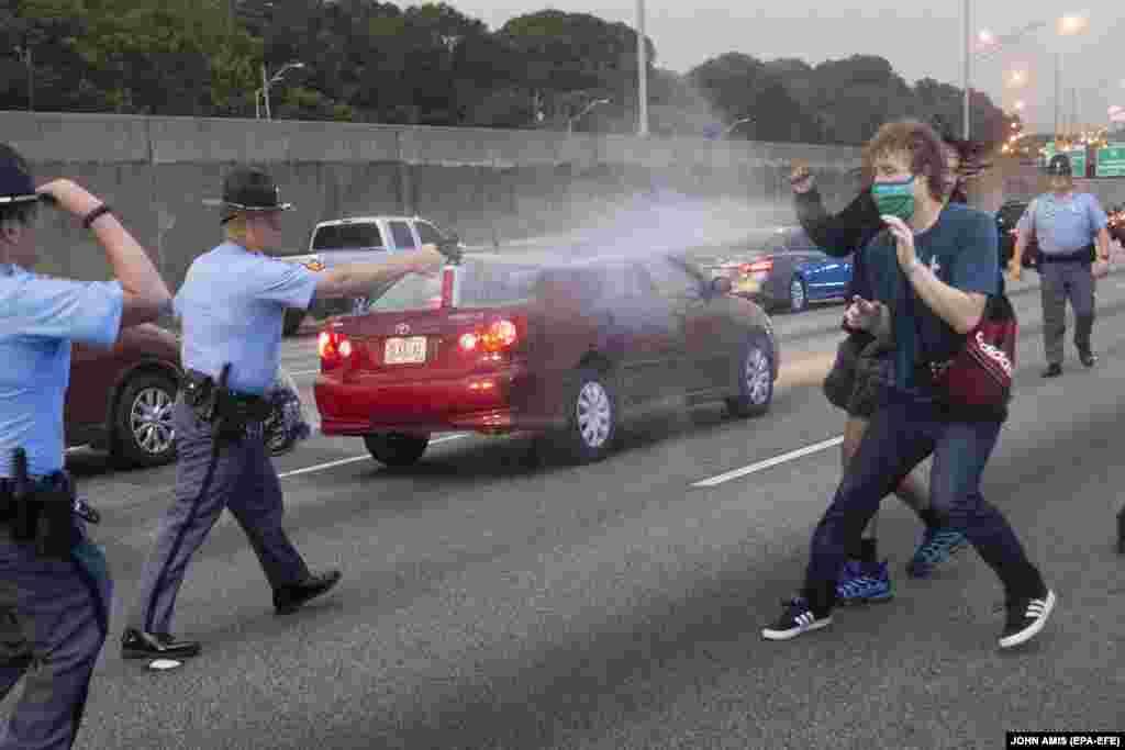 Правоохоронець використовує проти демонстрантів перцевий аерозоль після того, як група протестувальників вийшла на міждержавне шосе після протесту біля ресторану швидкого харчування Wendy's. Атланта, штат Джорджія, США
