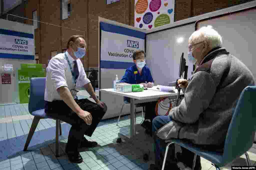 Саймон Стивенс (слева), исполнительный директор NHS (Национальная служба здравоохранения Соединенного Королевства), беседует с пациентом, который прибыл в центр вакцинации, чтобы получить дозу вакцины Pfizer/BioNTech COVID-19 в больнице Гая. Лондон, Великобритания, 8 декабря 2020 года