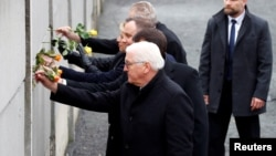 (Front to back:) German President Frank-Walter Steinmeier, Hungarian President Janos Ader, Polish President Andrzej Duda, Slovak President Zuzana Caputova, and Czech President Milos Zeman place roses into a gap in a Berlin Wall memorial during a ceremony marking the 30th anniversary of its fall.