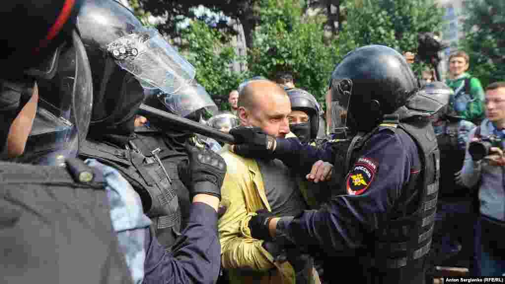 Резеңке таяқ ұстаған полиция наразылардың бірін тоқтатуға тырысып жатыр.