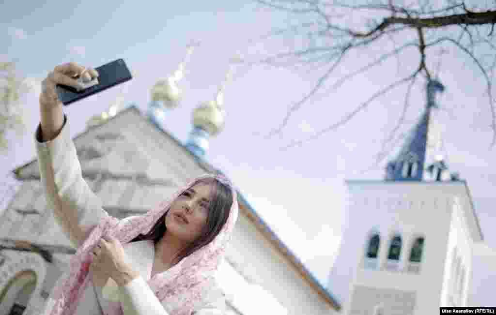 Прихожанка делает селфи у храма в Бишкеке.