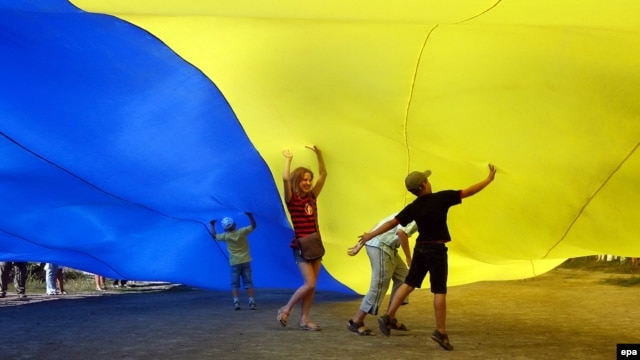Ukrainian children under a giant national flag in Kyiv in August 2010.