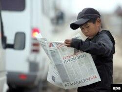Сайлау туралы газет мақаласын оқып тұрған қырғыз бала. Бішкек, 26 қазан 2011 жыл