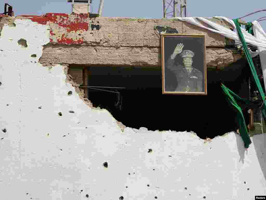 A picture of Libya's leader Muammar Qaddafi is seen on a damaged building in the centre of the city of Zawiyah on April 5. Photo by Zohra Bensemra for Reuters