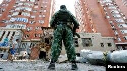 Вооруженный пророссийский сепаратист стоит у поврежденного в результате обстрелов здания. Донецк, 7 августа 2014 года.