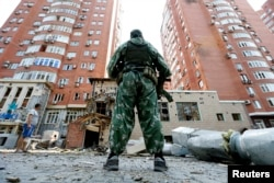 Донецкіде атыстан бүлінген ғимарат жанында тұрған қарулы ресейшіл сепаратист 7 тамыз 2014 жыл.