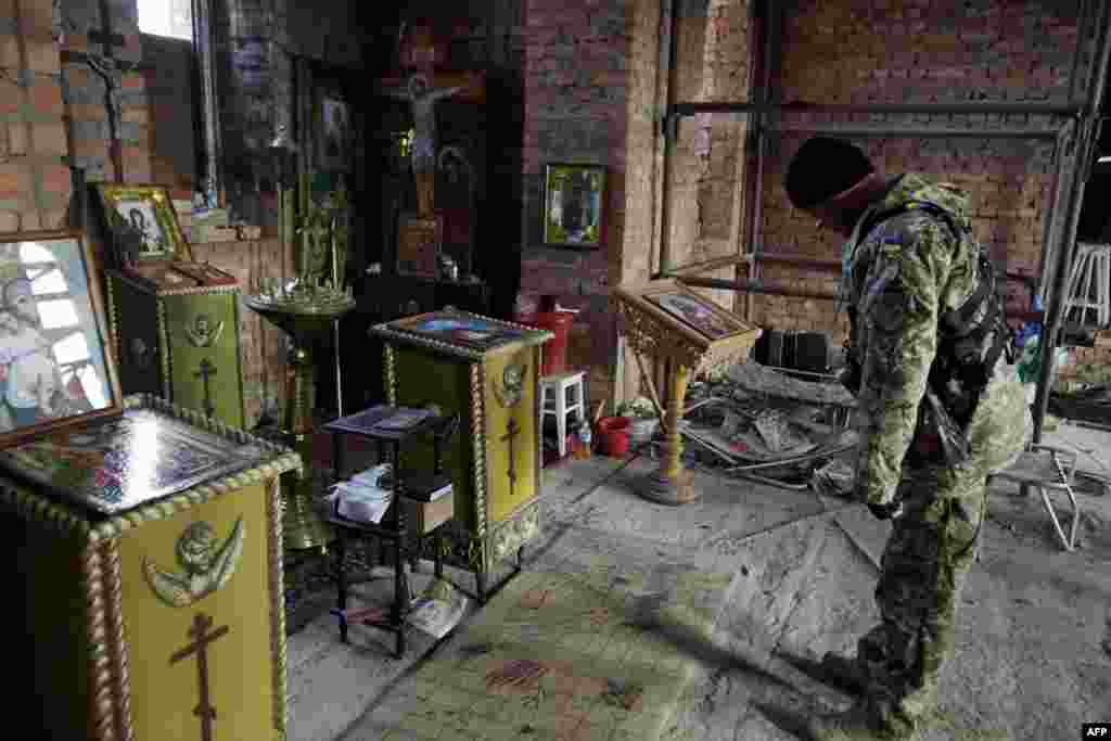 A Ukrainian serviceman visits an abandoned church in the village of Pisky near Donetsk. (AFP/Anatolii Stepanov)