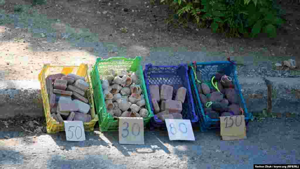 Местные жители продают отдыхающим раковины рапанов и куски пемзы