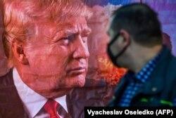 Беткапчан кыргызстандык тургун АКШнын президенти Д.Трамптын сүрөтү бар көрнөктүн жанынан өтүүдө. Бишкек. 2020-жылдын 7-ноябры.