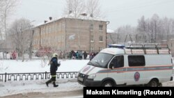 A vehicle from the Russian Emergencies Ministry stands parked near a local school in Perm after two assailants wearing masks injured schoolchildren and a teacher with knives on January 15.