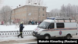 A vehicle from the Russian Emergencies Ministry is parked near the school in Perm after reports of a serious knife fight.