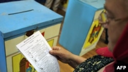 A woman reads her ballot at a polling station during local elections in Chisinau on June 5.