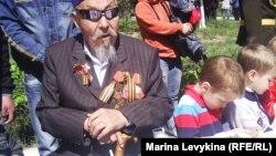 Участник Второй мировой войны рядом с детьми за праздничным столом после парада Победы. Семей, 9 мая 2012 года.