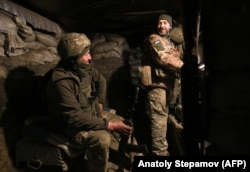 Ukrainian servicemen speak in their dugout on the front line with the separatists not far from Horlivka.