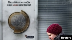 A pedestrian walks by a Eurobank advertisement featuring a 1-euro coin in Athens on February 8.