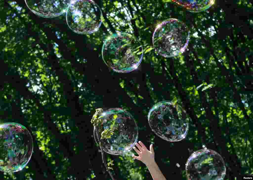 A child plays with soap bubbles at an event to support autistic children and their families in a park in the Ukrainian capital, Kyiv. (Reuters/Gleb Garanich)