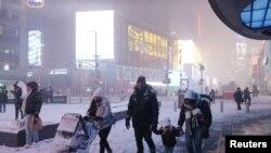 Люди ходят по улице Таймс-сквер, когда идет снегопад во время пандемии коронавируса (COVID-19) в районе Манхэттена Нью-Йорка, штат Нью-Йорк, США, 16 декабря 2020 г.