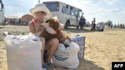 Дівчинка з Донбасу очікує на українсько-російському кордоні відбуття до табору для біженців у Ростов-на-Дону, серпень 2014 року
