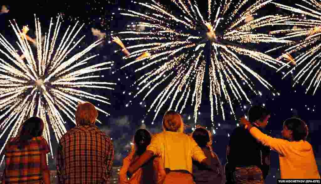 People look at a display during an international fireworks festival in Moscow's Brateyevsky Park. (epa-EFA/Yuri Kochetkov)