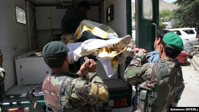 Afghan security forces retrieve one of the casualties from the attack and overnight siege at the popular Qargha Lake recreation area near Kabul that reportedly killed at least 20 people.
