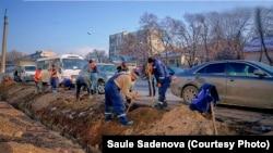 Рабочие выкорчевывают пни после вырубки деревьев у магазина Sulpak в Алматы. 26 ноября 2020 года.