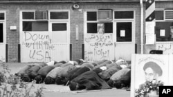 Iranian students pray inside the American Embassy compound before anti-American slogans on the third day of the occupation of the embassy in Tehran, Iran on Nov. 6, 1979. Sixty people are still held hostage against the deportation of the former Shah of Ir