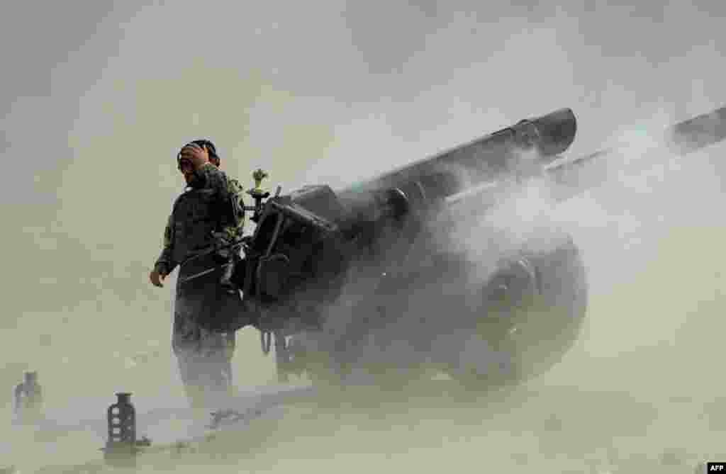 An Afghan National Army soldier fires an artillery shell during ongoing clashes between Afghan security forces and militants in the Kot district of Nangarhar Province. (AFP/Noorullah Shirzada)