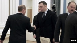 Putin (left) offers a hand to RusAl Chairman Deripaska (archive photo)