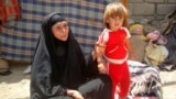 Iraq - An old woman with a kid in one of impoverished neighbourhoods in Kut, Kut, 18Aug2012
