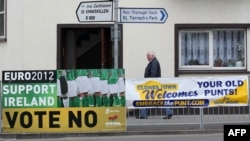 "A person walks past a placard on May 30 urging a ""no"" vote in the referendum on the EU fiscal pact and another sign that announces that the town, Clones, welcomes the old Irish currency, the punt."