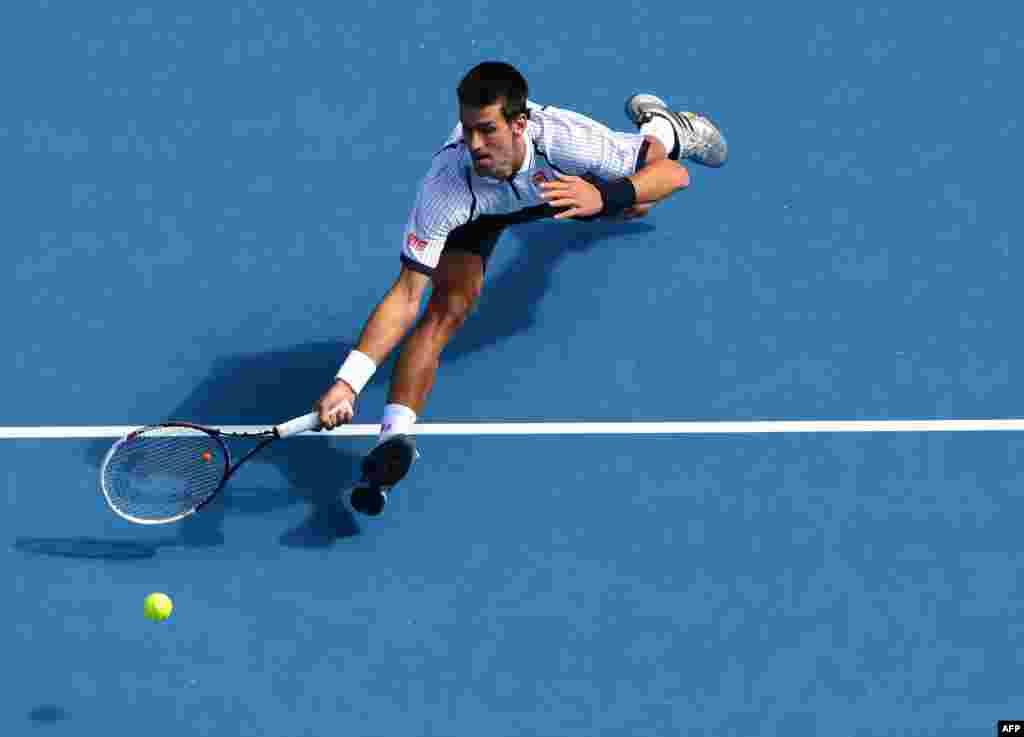 Serbia's Novak Djokovic stretches to return a shot during his men's singles match against Czech Republic's Radek Stepanek at the Australian Open tennis tournament in Melbourne. (AFP/William West)