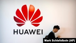 A man uses his smartphone as he stands near a billboard for Chinese technology firm Huawei at the PT Expo in Beijing, October 31, 2019. FILE PHOTO